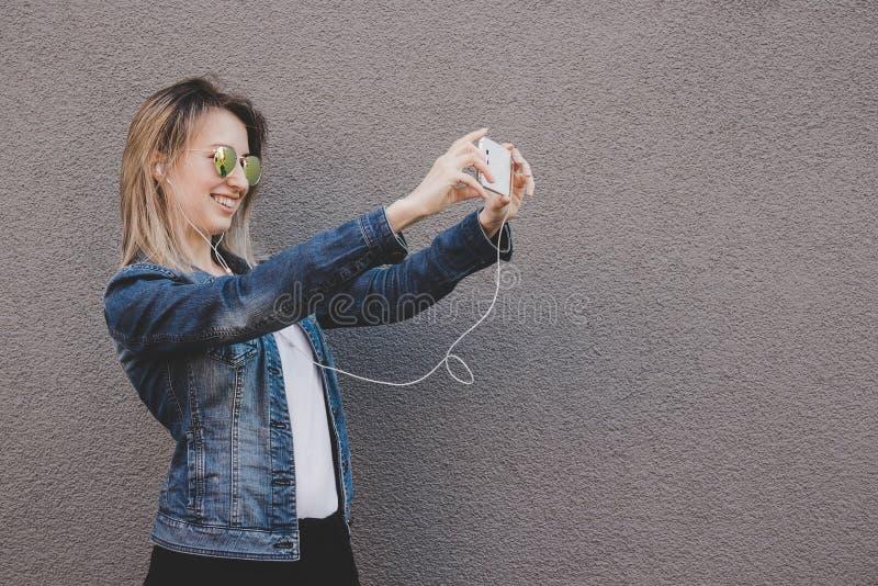 Ung le hipsterkvinna som tar selfie med hennes smartphone Grå färgbakgrund, kopierar utrymme royaltyfri foto