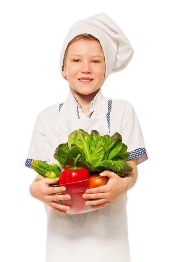 Ung le kock med bunken av nya grönsaker arkivfoton