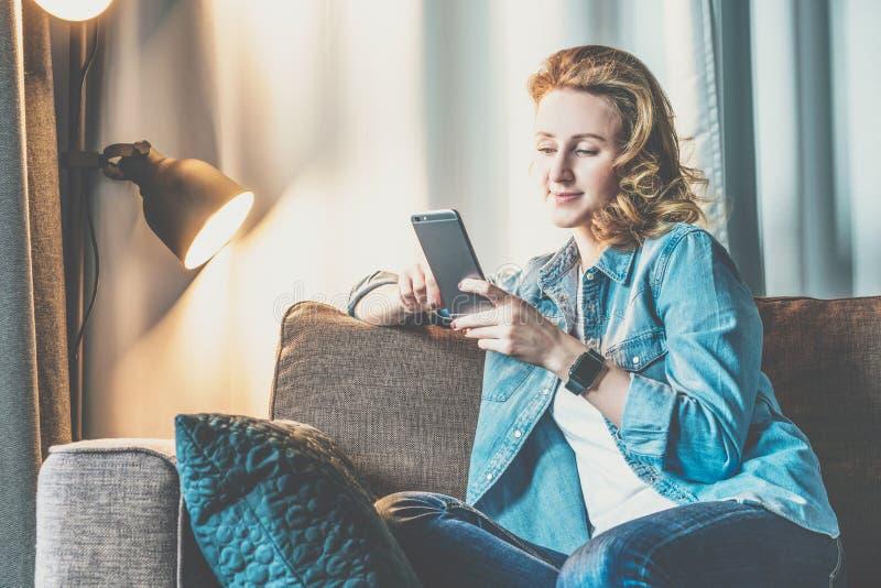 Ung le kvinna i grov bomullstvillskjortan som hemma sitter på soffan och använder smartphonen Flickan använder den digitala greje royaltyfri fotografi