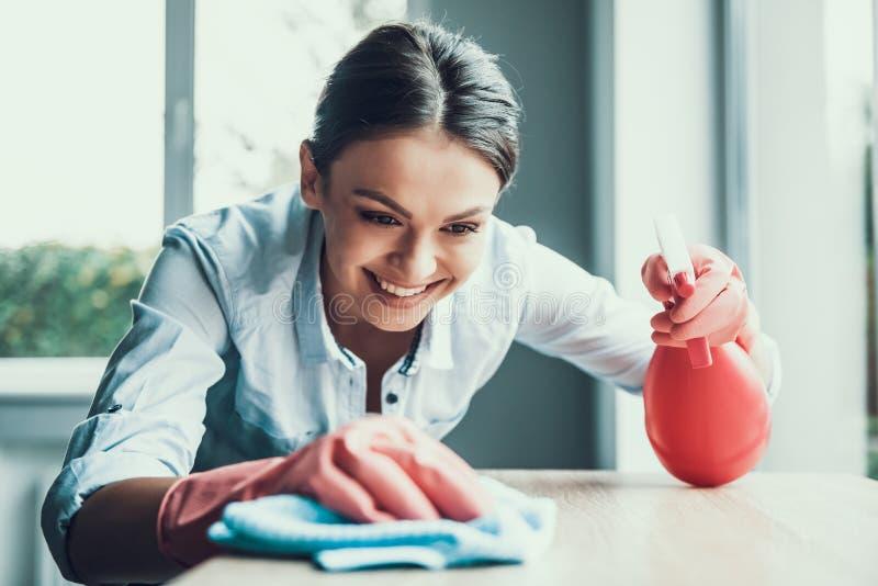Ung le kvinna i handskar som gör ren huset royaltyfria foton