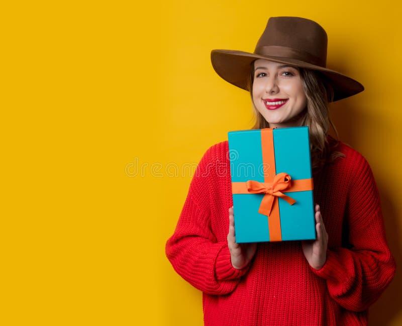 Ung le kvinna i röd tröja med gåvaasken royaltyfri fotografi