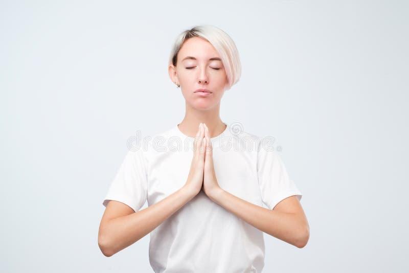 Ung le kvinna med kort kulört meditera för frisyr som rymmer hennes händer i yogagesten som känner sig lugna arkivbild