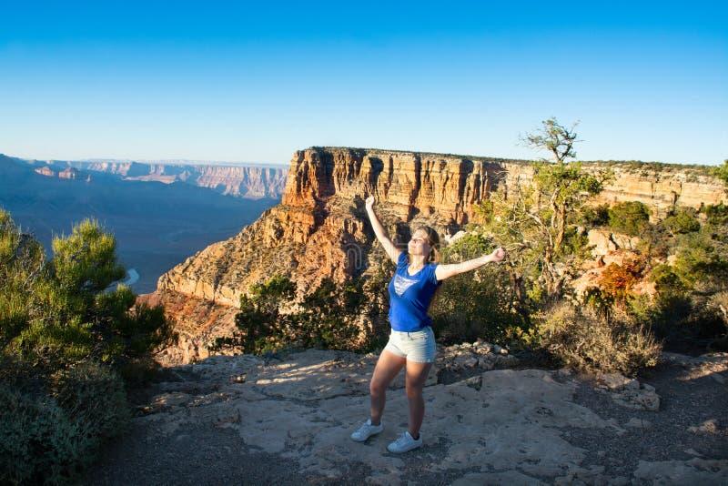 Ung le kvinna med lyftta armar som utomhus tycker om liv royaltyfria bilder