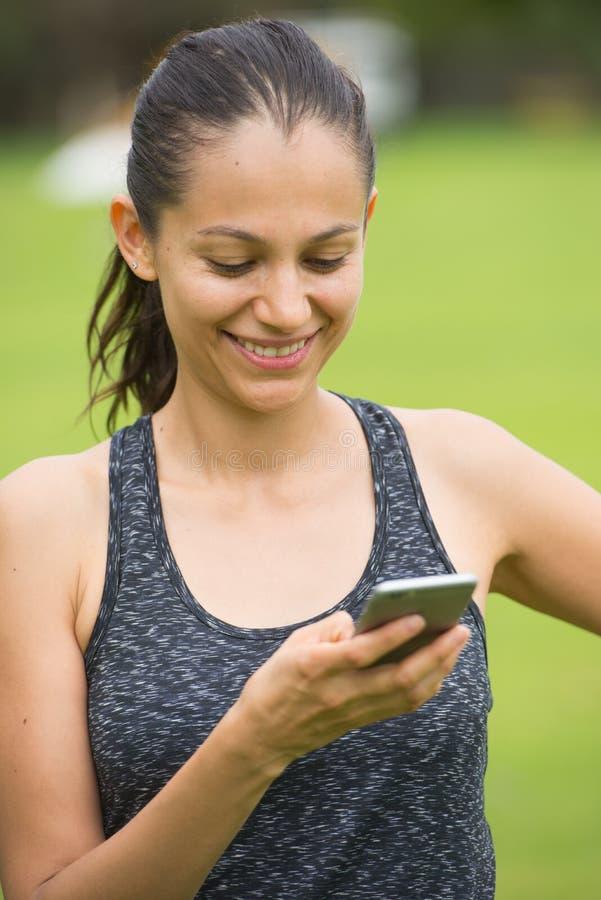 Ung le kvinna på den utomhus- smarta telefonen royaltyfri foto