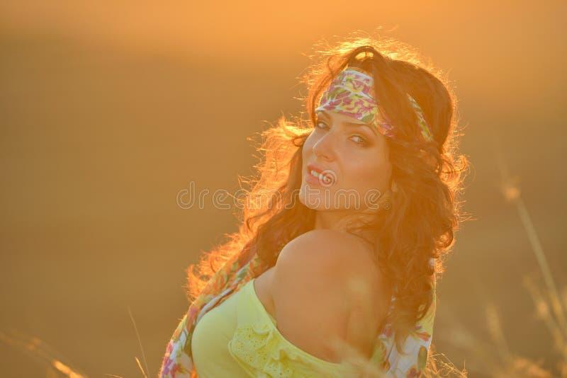 Ung le kvinna som är utomhus- i sommarsolnedgångljus arkivfoto
