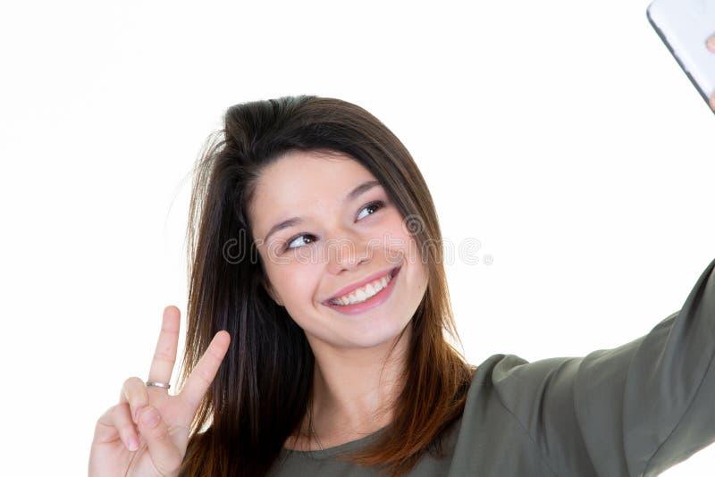 Ung le kvinna som tar en selfie med smartphonen som gör fredtecknet royaltyfria foton