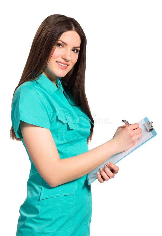 Ung le kvinnlig doktor i likformig med skrivplattahandstil fotografering för bildbyråer