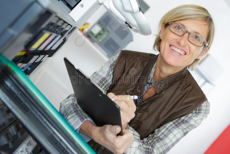 Ung le kvinnlig tekniker i overaller som rymmer skrivplattan royaltyfri foto