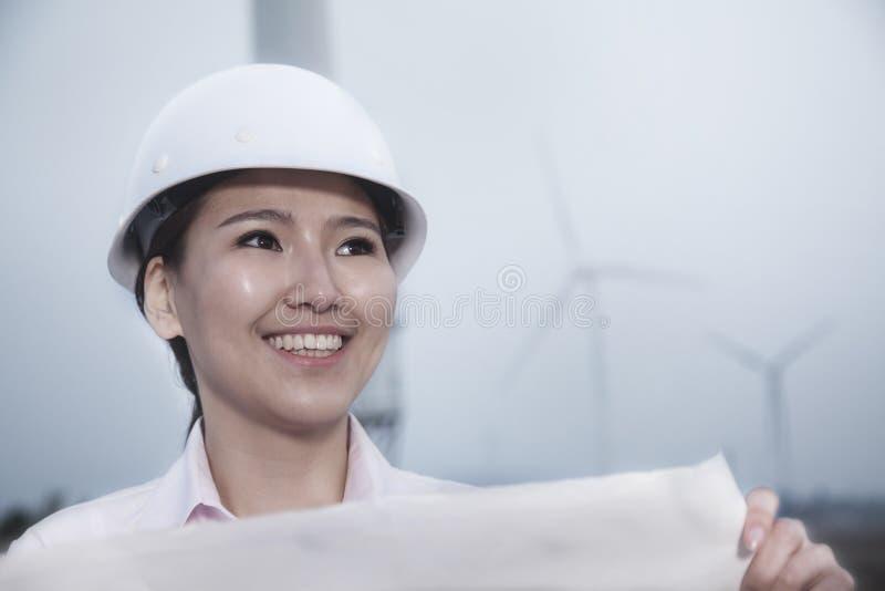 Ung le kvinnlig tekniker som rymmer en ritning med vindturbiner i bakgrunden royaltyfri bild