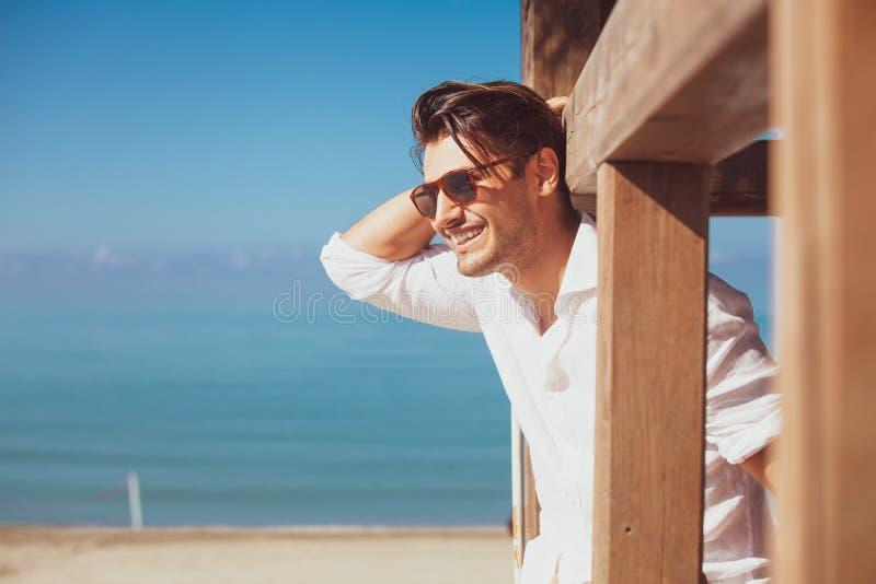 Ung le lycklig man på strandsemester royaltyfri foto