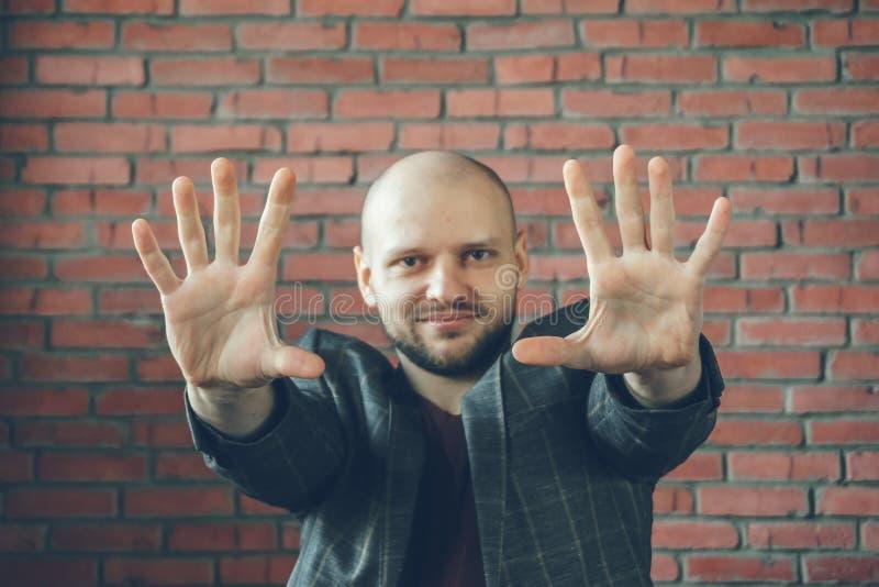 Ung le man med händer i luft som säger stopp- eller hypnotisörgest royaltyfri fotografi