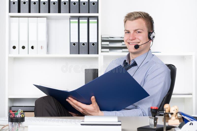 Ung le man med hörlurar med mikrofon och mapp i kontoret royaltyfri fotografi