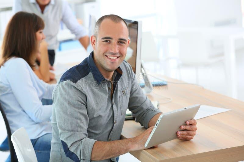Ung le man på kontoret genom att använda minnestavlan arkivfoton