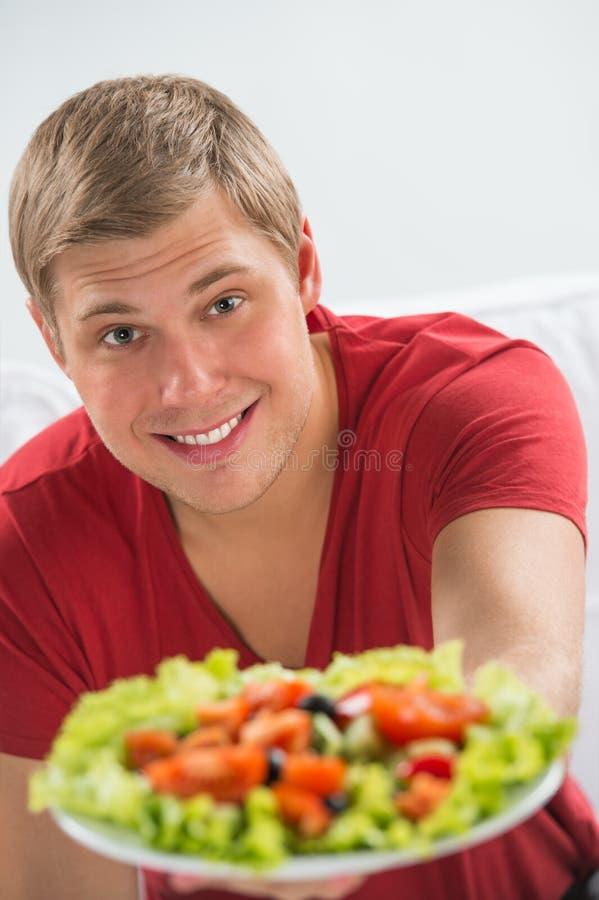 Ung le man som äter vegetarisk sallad arkivbild