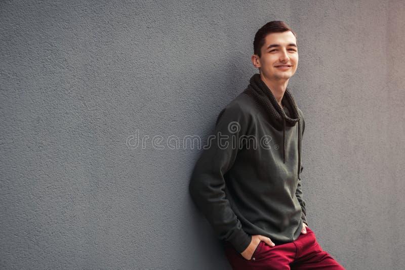 Ung le man som ser kameran mot den gråa väggen Grabb som utomhus bär tillfälliga kläder arkivfoto