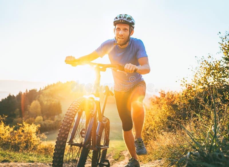 Ung le man som skjuter en mountainbike upp kullen Aktivt affärsföretaglopp på cykeln royaltyfri foto