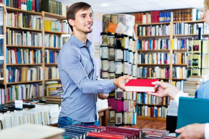 Ung le man som tar den valda boken från säljare royaltyfri foto