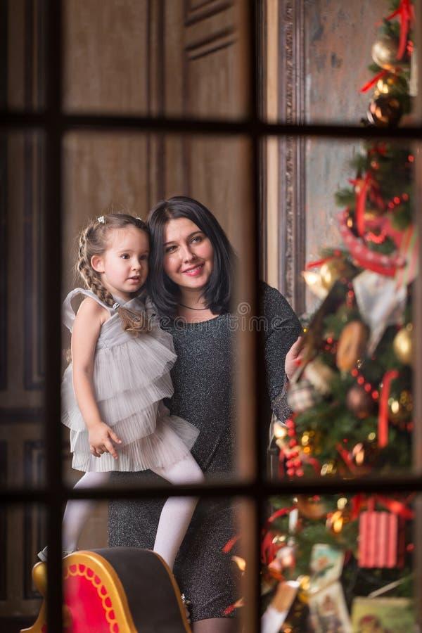 Ung le moder med den gulliga lilla flickan nära en julgran Fantastiskt familjferiebegrepp arkivbilder