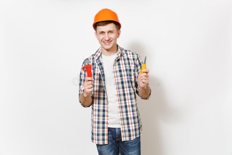 Ung le stilig man i skyddande orange skruvmejsel för hardhatinnehavleksak och justerbara skiftnyckeln som isoleras på vit arkivbild