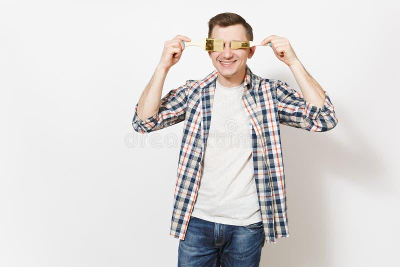 Ung le stilig man i tillfällig kläder som täcker ögon med målarfärgborstar som isoleras på vit bakgrund instrument royaltyfri bild