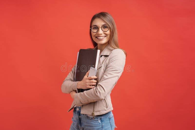 Ung le student eller allmäntjänstgörande läkare i glasögon som står med en mapp på röd bakgrund fotografering för bildbyråer