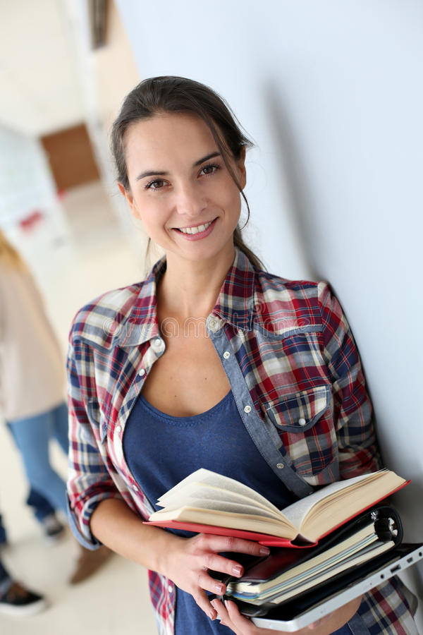 Ung le student med böcker i hall arkivbild