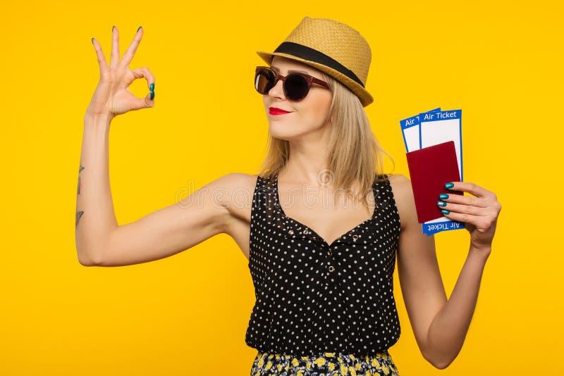Ung le upphetsad biljett för passerande för logi för pass för innehav för kvinnastudent som isoleras på gul bakgrund royaltyfria bilder