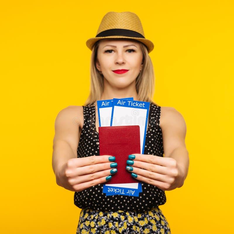 Ung le upphetsad biljett för passerande för logi för pass för innehav för kvinnastudent som isoleras på gul bakgrund Utbildning i royaltyfria bilder