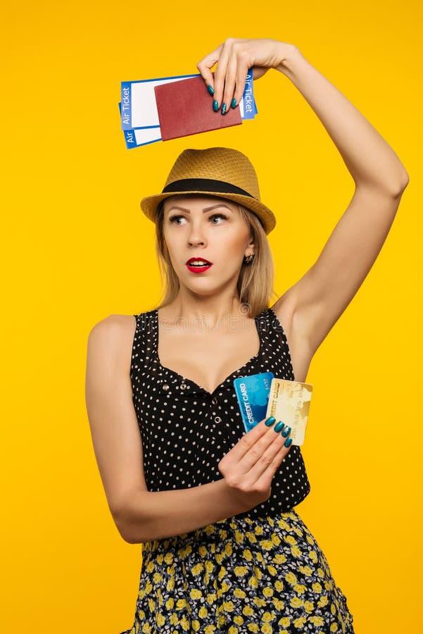Ung le upphetsad biljett och kreditkort för passerande för logi för pass för innehav för kvinnastudent som isoleras på gul bakgru royaltyfri bild