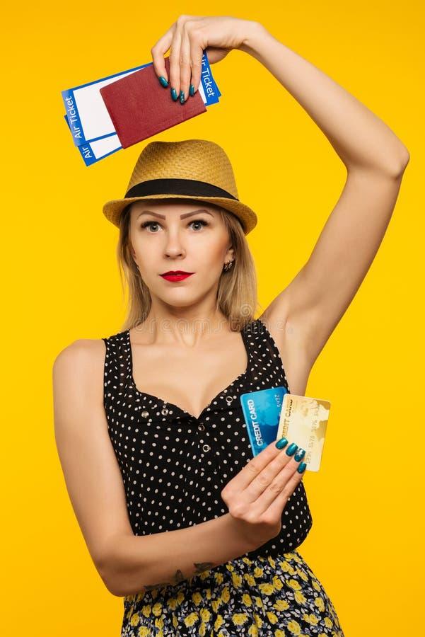Ung le upphetsad biljett och kreditkort för passerande för logi för pass för innehav för kvinnastudent som isoleras på gul bakgru arkivfoto