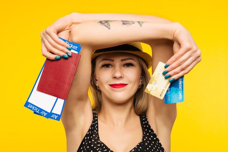 Ung le upphetsad biljett och kreditkort för passerande för logi för pass för innehav för kvinnastudent som isoleras på gul bakgru arkivbild