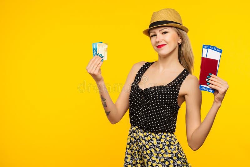 Ung le upphetsad biljett och kreditkort för passerande för logi för pass för innehav för kvinnastudent som isoleras på gul bakgru royaltyfri foto