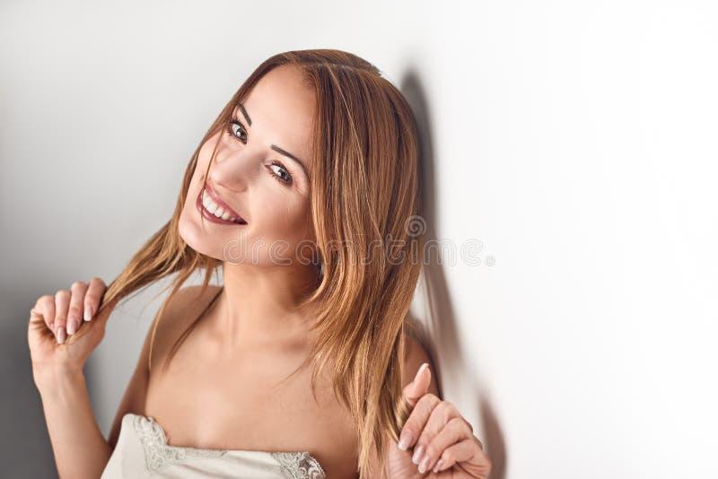 Ung le vägg för againt för brunettkvinna lutande royaltyfria foton