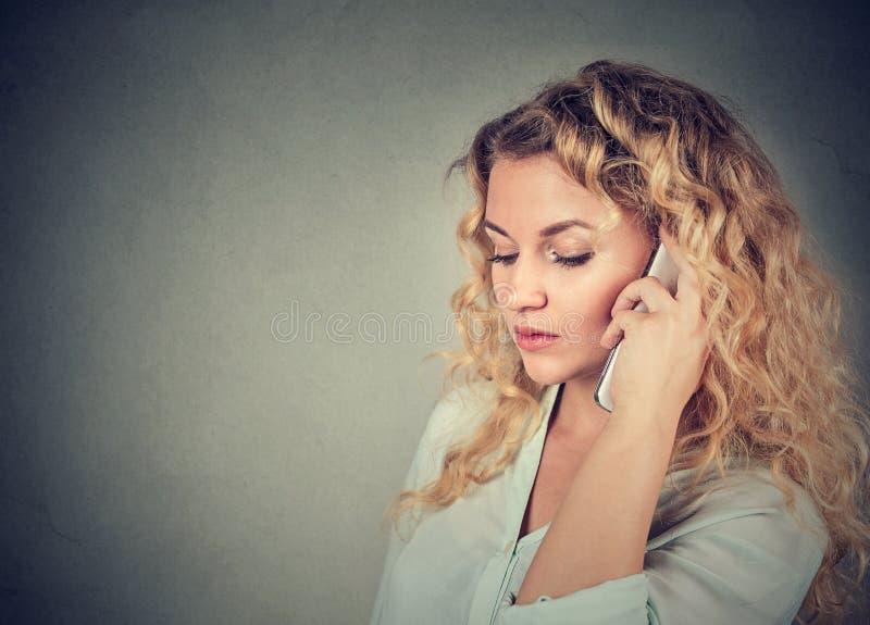 Ung ledsen kvinna som talar på mobiltelefonen royaltyfria foton