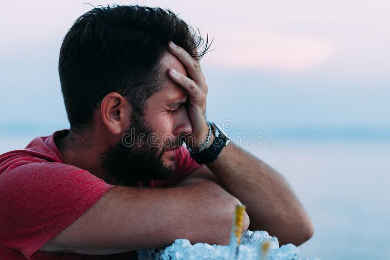 Ung ledsen man av havet som ser vatten arkivfoto