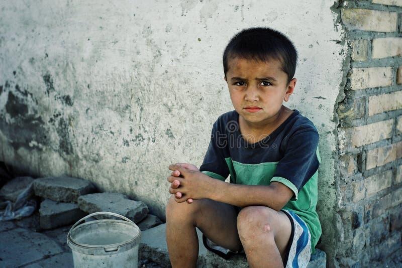 Ung ledsen seende pojke som mot efterkrav väntar på ett gatahörn något vatten från gemenskapreserven arkivfoton