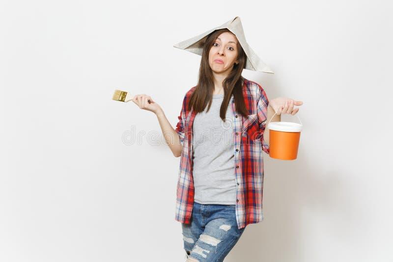 Ung likgiltig härlig kvinna i tidningshatten som rymmer målarfärgborsten, och målarfärghinken som isoleras på vit bakgrund arkivbild