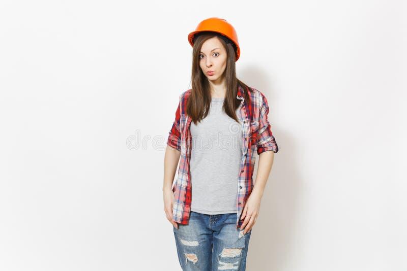 Ung likgiltig härlig kvinna i tillfällig kläder och hjälmen för skyddande konstruktion som orange isoleras på vit arkivfoto