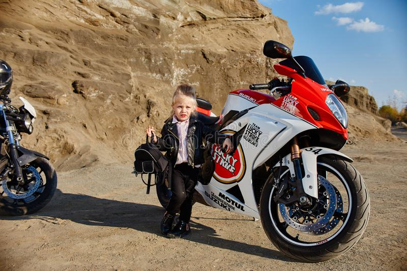 Ung liten flicka som sitter på en motorcykel som springer, härlig liten cyklist på en sportcykel i natur Dottern av en motorcykel royaltyfria foton