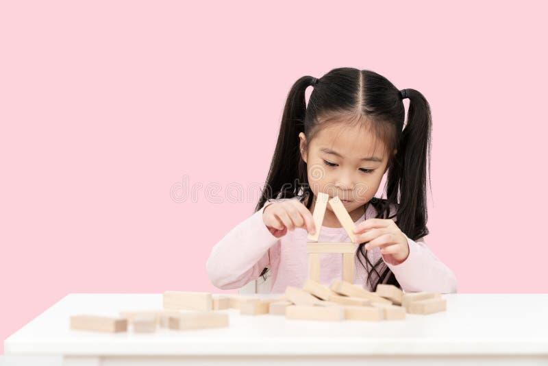Ung liten gullig asiatisk flicka att bygga ett hus från träkvarterkonstruktion, träleksak, jengahus på skrivbordet i isolerade ro royaltyfria foton