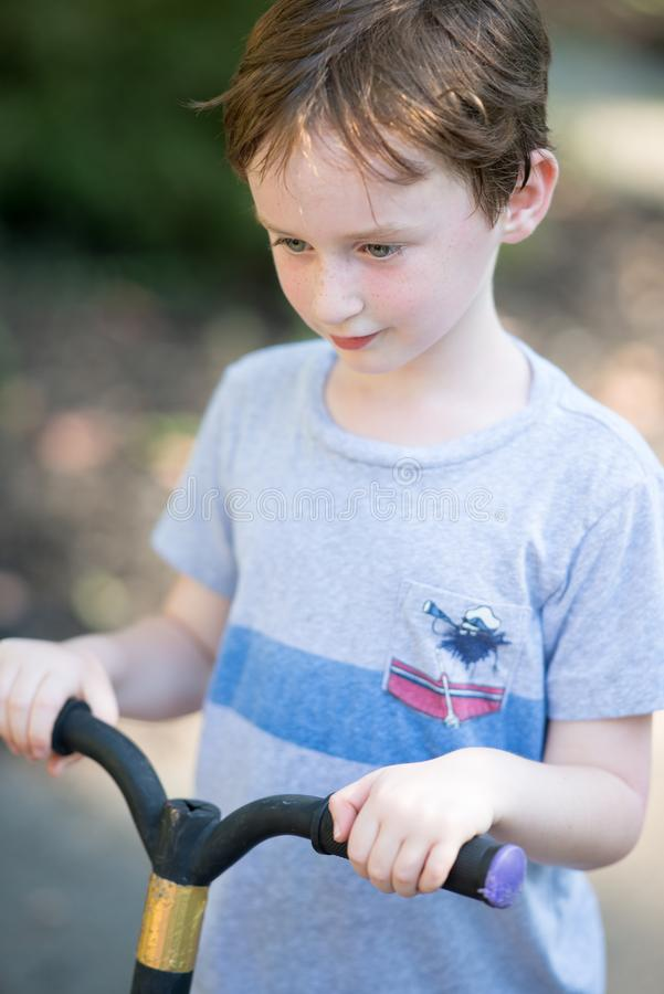 Ung littepojke utanför att rida hans sparkcykel i körbanan arkivbild