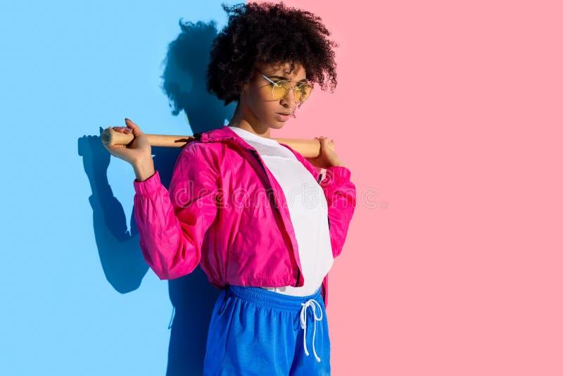 Ung ljus afrikansk amerikanflicka med baseballslagträet på hennes skuldror på rosa färger och blått royaltyfri foto