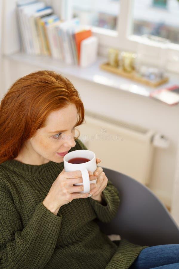 Ung ljust rödbrun kvinna som hemma dricker te royaltyfri fotografi