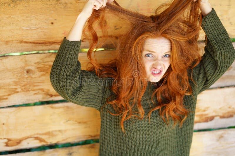 Ung ljust rödbrun kvinna som spelar med hår utomhus arkivbild