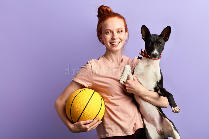 Ung ljust rödbrun lycklig flicka som spelar med hennes hund fotografering för bildbyråer