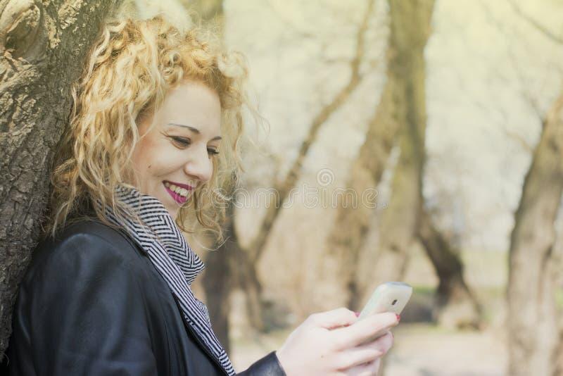 Ung lockig blond kvinnamaskinskrivning på telefonen i utomhus royaltyfria bilder