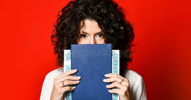 Ung lockig flicka för Closeupstående som döljer bak ett öppet bokomslag, på den röda bakgrundsväggen royaltyfri bild