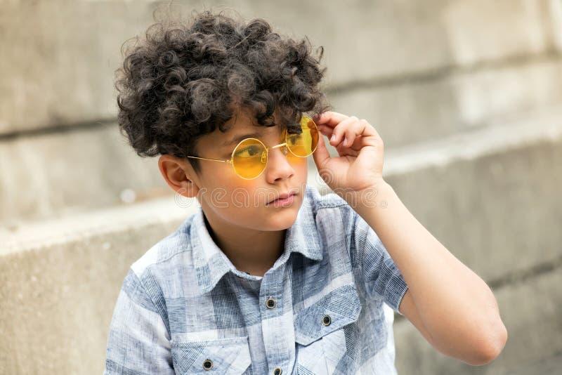 Ung lockig hövdad pojke med moderiktiga gula skuggor arkivbild