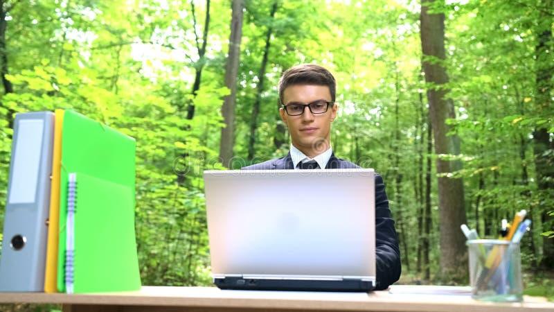 Ung lovande chef mycket av idérika idéer som utomhus arbetar i grön skog royaltyfri fotografi