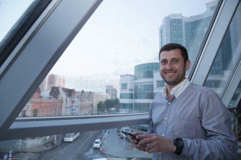 Ung lyckad affärsman med ett leende på hans framsidablickar på nyheterna på en mobiltelefon på bakgrunden av ett panorama- fönste royaltyfri foto
